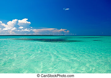 Cyan ocean under blue sky with clouds in summer