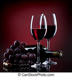 Wine in glasses with grape and bottle on red