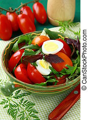 Fresh salad with tomato and quail eggs in bowl on a green...