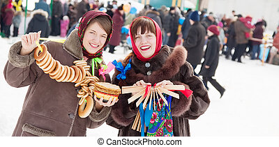 girls plays during Shrovetide at Russia - Two happy girls...