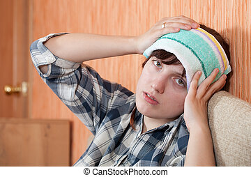 woman having headache holding towel on her head