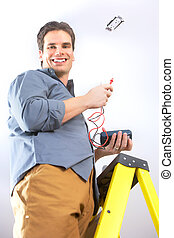 electrician - Young smiling electrician doing his work