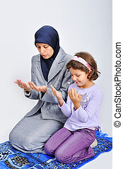 Young muslim woman praying on traditional way with her daughter
