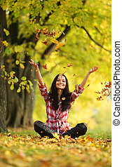 woman drop leaves in autumn park - woman drop up leaves in...
