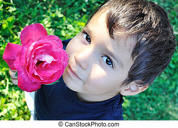 Very cute child with a pink rose in his hand