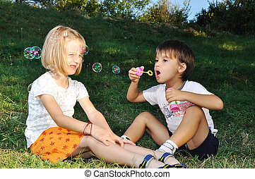 Happy childhood in summer outdoor, with bubbles