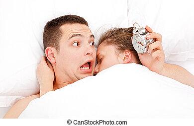 Man waking up lately near a woman