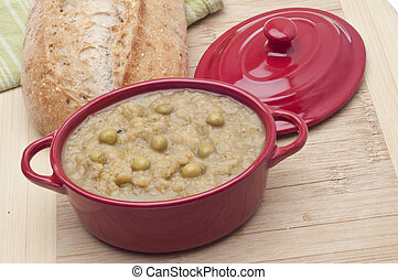 Split Pea Soup in a Crock with Bread in the Background.