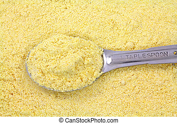 Stone ground yellow corn meal with tablespoon - A filled...