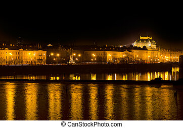 The Prague National Theater and the Vlava river at night -...