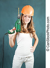 Female construction worker in a hard hat with drill