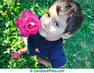 Very cute little boy with rose outdoor, closeup
