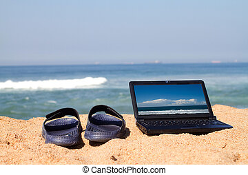 laptop and slippers on beach