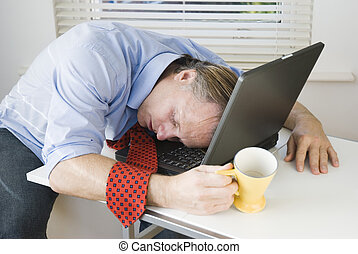 Exhausted businessman - A tired businessman asleep on top of...