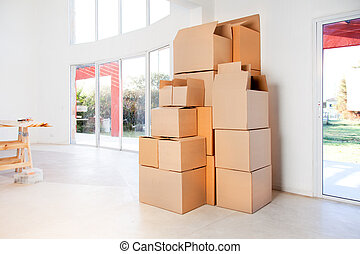 Moving Boxes - A stack of moving boxes in a new house, ready...