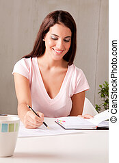 Business Plan - A woman making business plans sitting at a...
