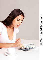 Home Finances - A woman sitting at a table with calculator,...