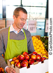 Grocery Store Peaches - A happy male grocer with a box of...