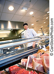 Fresh Meat Counter - A butcher looking at a fresh meat...