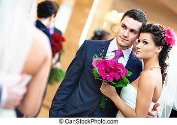 Young wedding couple looking at mirror