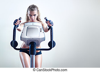 Young woman on exercise bicycle
