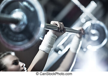 Young woman weight training Focus on hand