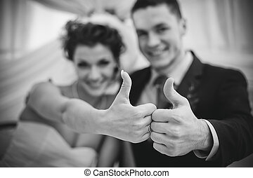 Young wedding couple showing success sign Focus on hands