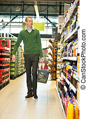 Man walking in grocery store - Mid adult man with shopping...