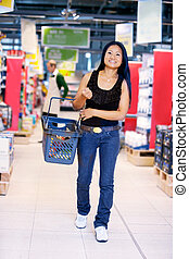 Asian Woman in Grocery Store - Smiling asian woman walking...
