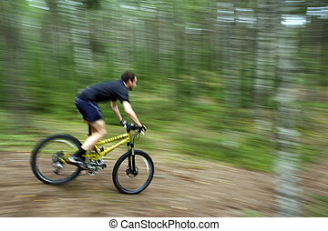 Mountain biker going down the hill with motion blur