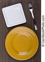 Table appointments - Ceramic plates for table on a brown...