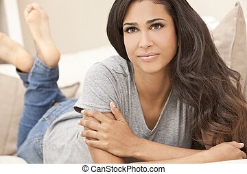 Beautiful Hispanic Woman Laying on Sofa Relaxing & Smiling -...