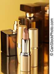 Cosmetics on gold - Set of perfumes and lipsticks on gold...