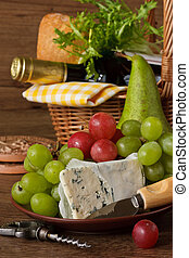 Basket for picnic. - Grapes, cheese, pear and bottle of...