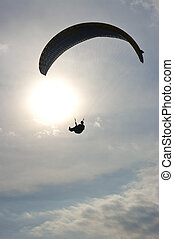 Paraglider with rising sun in background