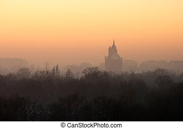 Cityscape with park and fog during the sunset