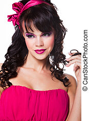 Portrait of beautiful girl with dark hair wearing pink on...