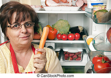 Refrigerator close up with mature woman