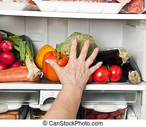 Refrigerator - Woman hands grab vegetables from refrigerator