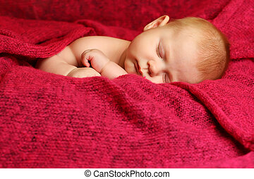 Newborn baby sleeping  on a red blanket
