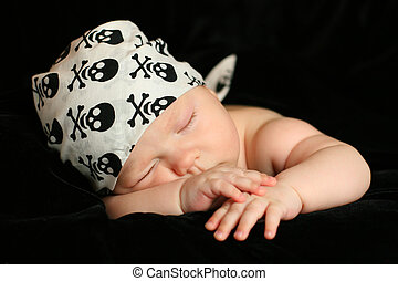 Newborn baby sleeps in a white bandana black background