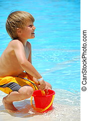 Boy with sand bucket - A view of a young boy playing in...