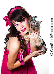beautiful girl with dark hair wearing pink holding small dog on white background