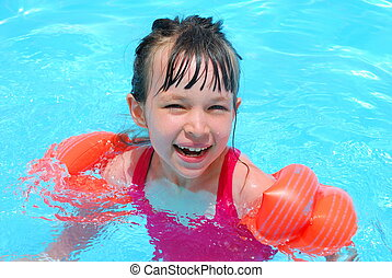 Happy swimming girl laughing in the pool.