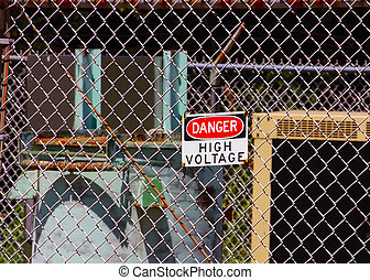 High Voltage Sign - A high voltage sign fastened to a fence.