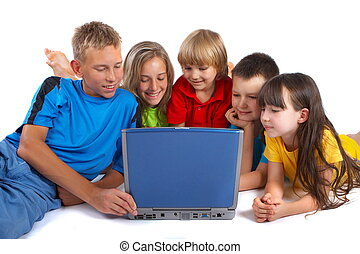 Sharing a laptop - A group of children huddle together to...