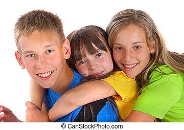 Loving siblings - Three siblings hug each other close,...