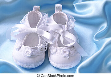 White baby booties on blue silk