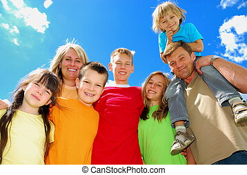 Family - A happy family stands together under the clear sky,...