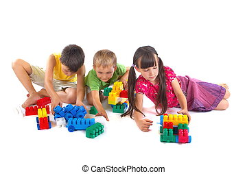 Playing children with constructing sets and toys.